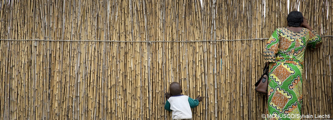 Woman child look through a bamboofence MONUSCOPhotos cc